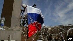 4月7日,一面戴上面罩手持俄羅斯國旗的示威者爬上烏克蘭涅茨克州政府大樓。