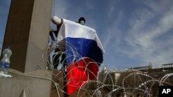 Donetsk kentinde bir hükümet binası önünde kurulan barikatın üzerinde Rus bayrağı sallayanmaskeli bir gösterici