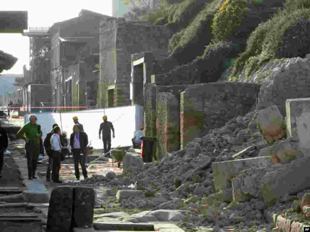 People survey damage from the 2010 collapse of a house used by gladiators in Pompeii. (Reuters)