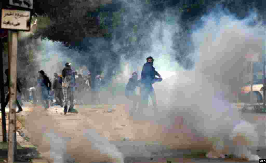 14 Ocak: Tunus'ta polise taşlarla karşılık veren göstericiler. Normalde oldukça sakin olarak bilinen Tunus'ta çıkan ayaklanmalar, Devlet Başkanı'nın ülkeyi terk etmesiyle sonuçlandı. (Christophe Ena/AP)