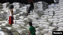 A worker passes a sack of rice to other workers inside a National Food Authority (NFA) warehouse in Taguig City, south of Manila, the Philippines, March 26, 2012.