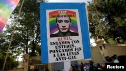 FILE - A member of the LGBT community holds a placard with the picture of Russia's President Vladimir Putin during a protest outside the Russian Embassy against discrimination and violence aimed at gays in Chechnya and other regions of Russia, in Mexico City, Mexico, April 19, 2017.