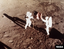"In this July 20, 1969 file photo, Apollo 11 astronauts Neil Armstrong and Edwin E. ""Buzz"" Aldrin, the first men to land on the moon, plant the U.S. flag on the lunar surface. Photo was made by a 16mm movie camera inside the lunar module, shooting at one f"