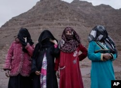In this March 30, 2019 photo, the first female Bedouin guides, from right, Selima, Umm Yasser, Umm Soliman, and Aicha, pose for a photograph in Wadi Sahw, Abu Zenima, in South Sinai, Egypt. Four Bedouin women are for the first time leading tours in Egypt