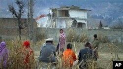 Một gia đình người Pakistan ngồi xem giới hữu trách phá đổ khu nhà của bin Laden ở Abbottabad, Pakistan hồi tháng 2 năm 2012