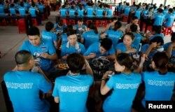 Para pekerja perempuan makan siang bersama rekan-rekan pria di pabrik garmen Maxport di Provinsi Thai Binh, Vietnam, 13 Juni 2019. (Foto: Reuters)