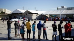 Migrants from Haiti, who returned to the Mexican side of the border to avoid deportation, queue for breakfast at a shelter set by the National Migration Institute (INM) in Ciudad Acuna, Sept. 25, 2021.