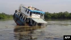 A Bangladeshi tanker sinks in the Sela River in the Sundarbans, spreading oil that threatens the environment, Dec. 9, 2014.