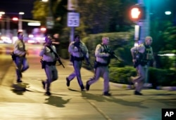 Police run to cover at the scene of a shooting near the Mandalay Bay resort and casino on the Las Vegas Strip, Oct. 1, 2017, in Las Vegas.