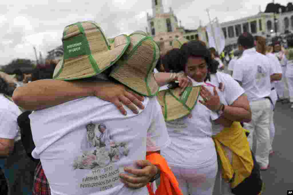 A group of pilgrims from Lisbon embrace after their arrival at the Sanctuary of Our Lady of Fatima, in Fatima, Portugal. On Saturday Pope Francis will canonize two poor, illiterate shepherd children whose visions of the Virgin Mary 100 years ago marked one of the most important events of the 20th-century Catholic Church.