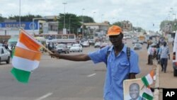 Vendeur de fanions et de portraits du président Alassane Ouattara à Yamoussoukro, le 21 mai 2011