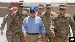 US Secretary of Defense Robert M. Gates walks with a group of service members at Forward Operating Base Waltman, Kandahar, Afghanistan, June 5, 2011