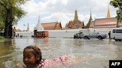 Một bé gái bơi trong dòng nước lụt phía trước Hoàng Cung Thái Lan
