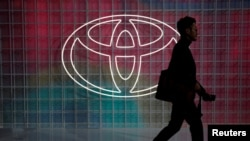 Un hombre pasa por delante del logotipo de Toyota en Tokio, Japón. [Foto de archivo]
