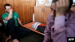 Người thân của bé Ali Saad Dawabsha ngồi khóc bên cạnh thi thể của em trong tang lễ tại làng Duma, 31/7/2015.