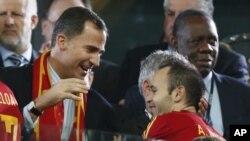Pangeran Felipe dari Spanyol (kiri) merayakan kemenangan tim matador dalam Piala Eropa bersama Andres Iniesta (kanan) (foto: 2/7). Iniesta dinobatkan sebagai pemain terbaik kejuaraan Eropa.
