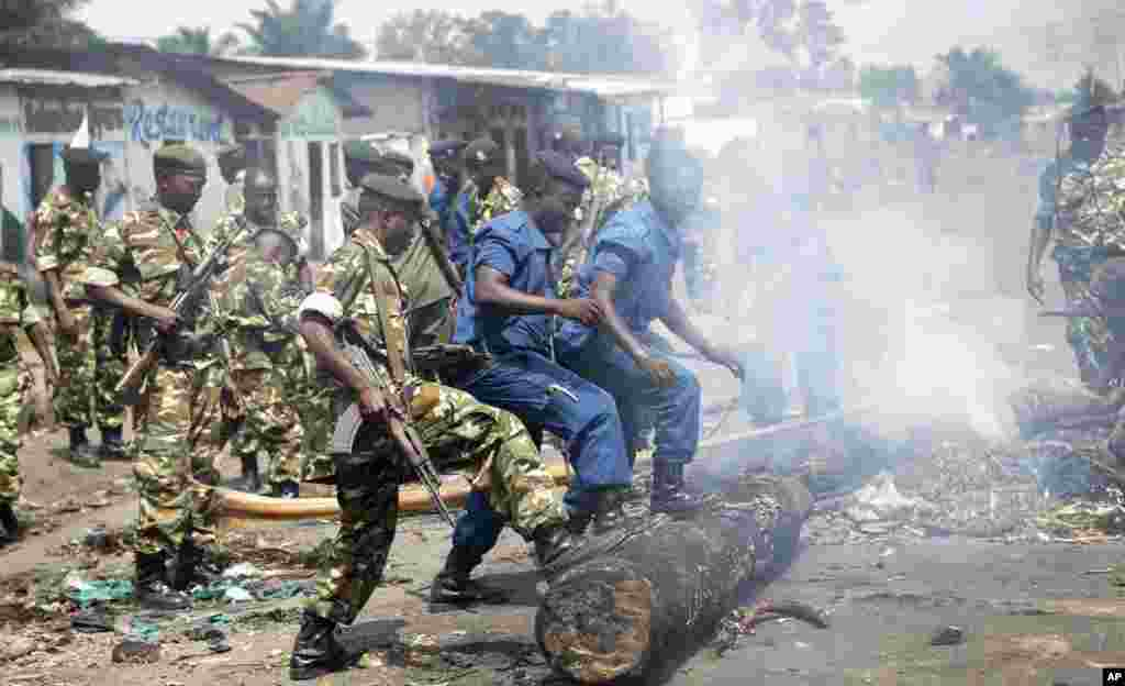 Police and army clear barricades set by opposition demonstrators in the Cibitoke district of the capital Bujumbura, May 25, 2015.