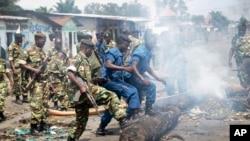 Des miliaires et policiers burundais dégagent d'une voie publique des barricades érigées par des manifestants opposés à un troisième mandat du président Pierre Nkurunziza