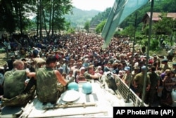 FILE - A Thursday July 13, 1995 photo from files showing Dutch UN peacekeepers sitting on top of an APC while Muslim refugees from Srebrenica, eastern Bosnia, gather in the village of Potocari