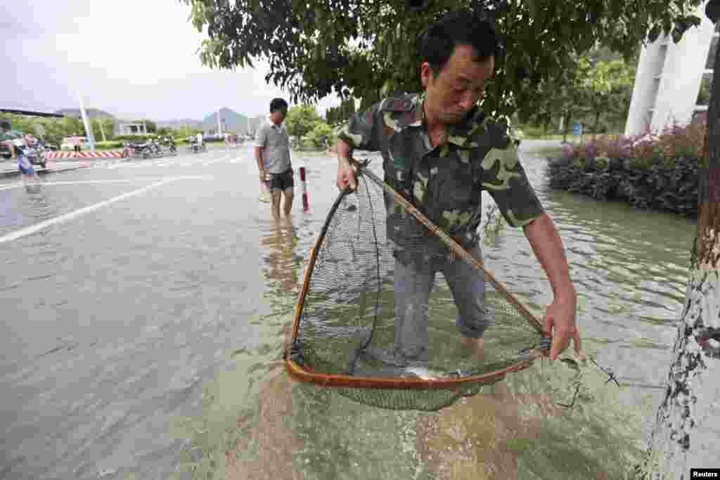 A man fishes on a flooded street after Typhoon Haikui hit Taizhou, Zhejiang province, China, August 8, 2012.