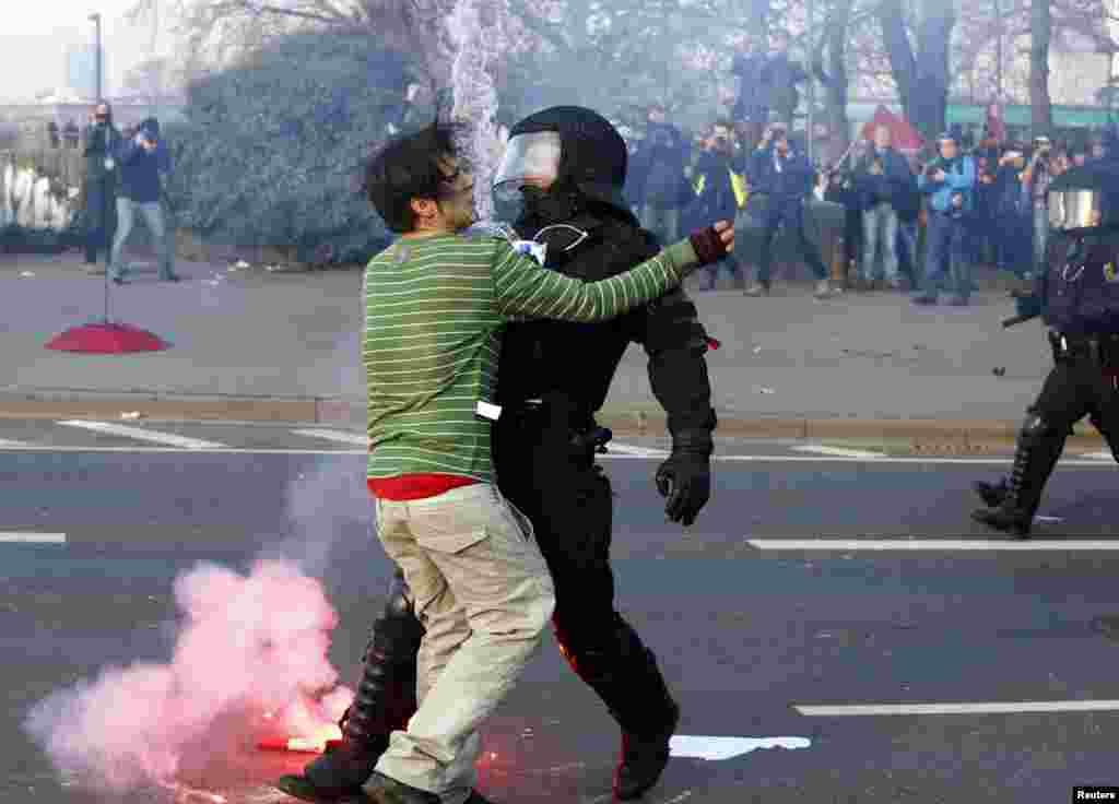 تظاهرات گسترده ای در فرانکفورت آلمان عليه گشايش شعبه بانک مرکزی اروپا در اين شهر صورت گرفت. در اين عکس، يک مامور پليس تظاهر کننده ای را از نزديک شدن به ساختمان بانک برحذر می کند.