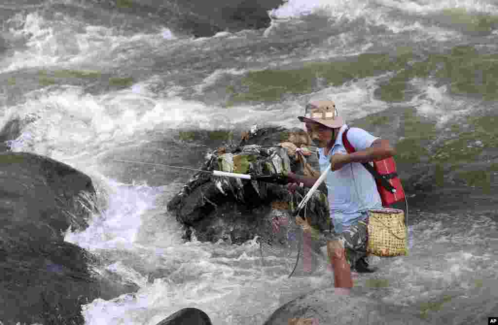 A man uses a net to catch fish in a stream in Bogor, West Java, Indonesia.