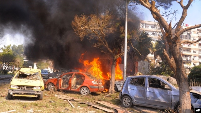 This photo released by the Syrian official news agency SANA, shows flames and smoke rising from burned cars after a huge explosion that shook central Damascus,February 21, 2013.