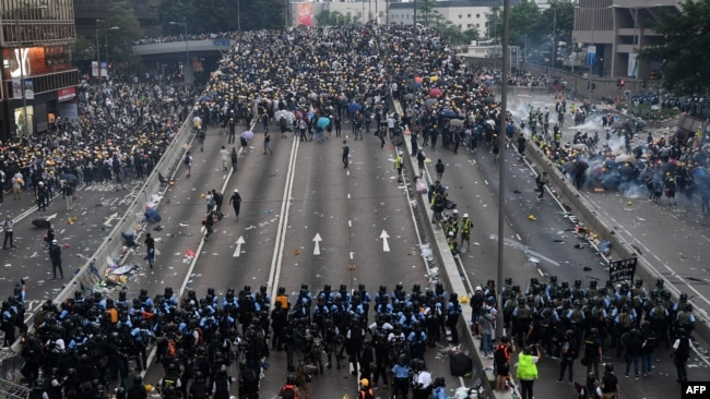在香港警察施放催淚瓦斯後,抗議者在政府總部外與警方對峙。 (2019年6月12日)