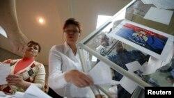 Para anggota komisi pemilu lokal mengosongkan kotak suara untuk menghitung suara dalam referendum untuk status wilayah Donetsk di Ukraina Timur (11/5).