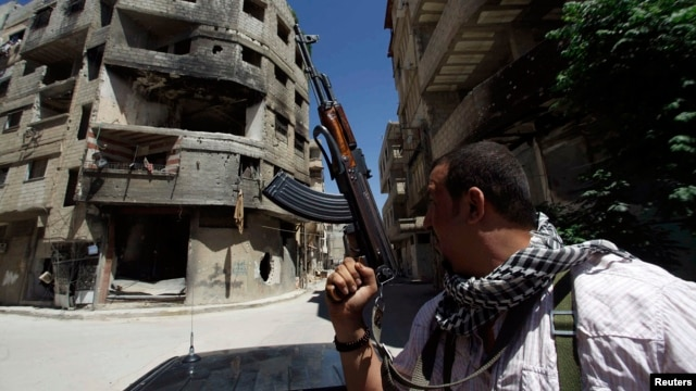 A Shi'ite fighter holds his weapon while patrolling a road at Sayeda Zainab area in Damascus, May 26, 2013.