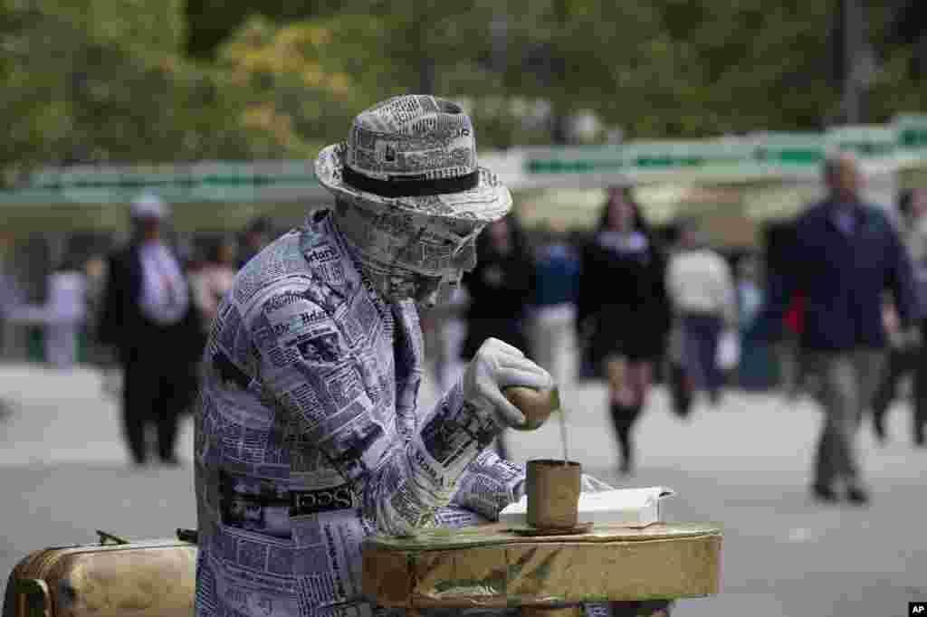 Một nghệ sĩ phủ báo khắp người và đọc một cuốn sách trong ngày khai mạc hội chợ sách hàng năm ở Madrid, Tây Ban Nha.