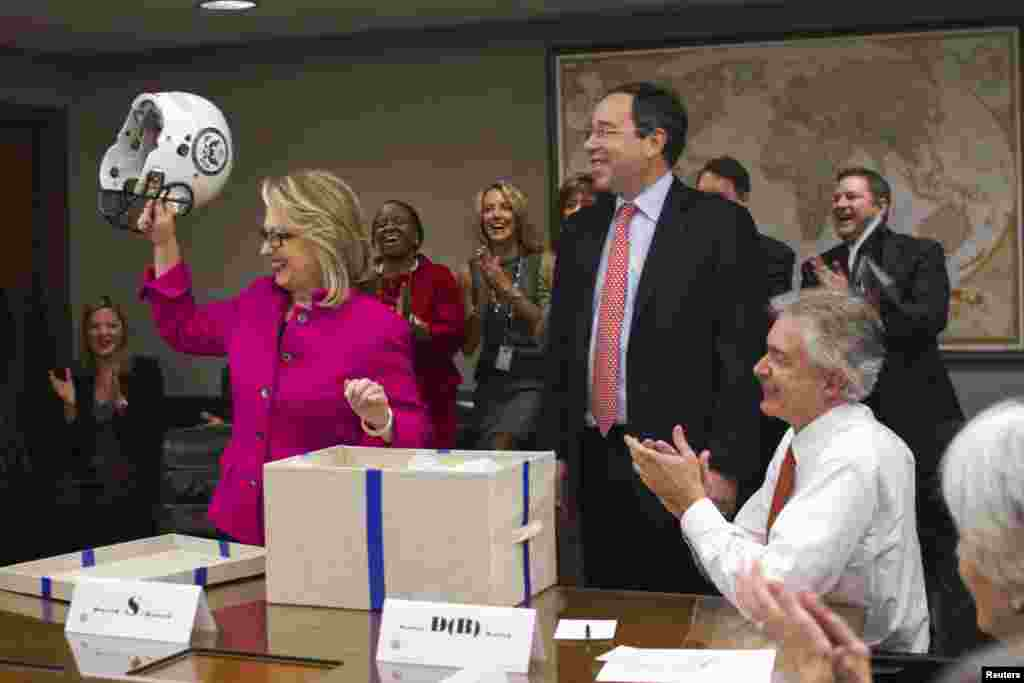 U.S. Secretary of State Hillary Clinton holds up a football helmet with the State Department logo on it, presented by Deputy Secretary of State Thomas Nides (C), who joked that 'Washington is a contact sport,' January 7, 2013. Clinton resumed her official duties, five days after being released from a hospital for treatment of a blood clot.