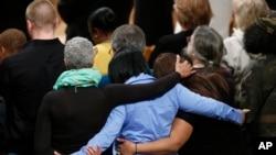Para pelayat di Katedral Nasional di Washington saling merangkul saat berdoa untuk korban penembakan di Sandy Hook Elementary School di Newtown, Connecticut, 12 Desember 2013.