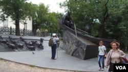 """莫斯科街头苏联作家肖洛霍夫和他的作品""""静静顿河""""为背景的塑像。(美国之音白桦拍摄)"""