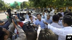 Rong Chhun, rear center, Cambodian Teacher Independence Association's president gives a press conference on a street as he walking to the protesting site to mark the two-year anniversary of Thai troop crossing border in Phnom Penh, Thursday, July 15, 2010.