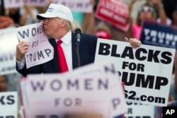 """美国共和党总统候选人唐纳德·川普亲吻标语""""妇女支持川普""""(2016年12月12日)"""