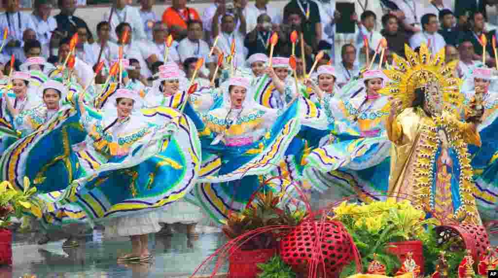 گروهی از هنرمندان فيليپينی رقص سنتی «سينولاگ» را در برابر پاپ فرانسيس پيش از آغاز عشاء ربانی، اجرا میکنند.