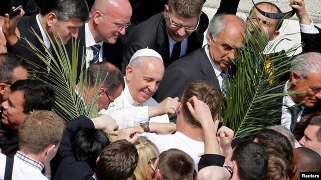 Pope Francis greets young people after leading Palm Sunday mass, at St Peter's Square in the Vatican April 13, 2014.