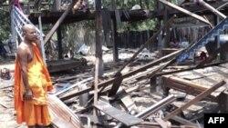 Vị sư Kampuchea nhìn cảnh nhà cửa nằm gần khu vực biên giờ đang tranh chấp giữa Thái Lan-Kampuchea đổ nát vì đạn pháo
