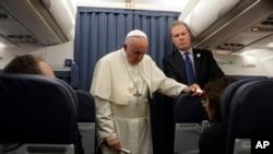 DGH Phan-xi-co (phải) và Phát ngôn viên Vatican Greg Burke, lắng nghe câu hỏi của một nhà báo trong một cuộc họp báo trên chuyến bay tới Roma sau khi kết thúc chuyến thăm Ireland hôm Chủ nhật 26/8/2018. (AP Photo/Gregorio Borgia, Pool)