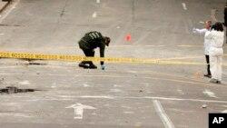 Policía e investigadores inspeccionan el sitio donde una bomba casera explotó cerca de la plaza de toros de Santamaría en Bogotá, Colombia, el domingo 19 de febrero de 2017.