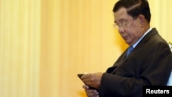 FILE - Cambodia's Prime Minister Hun Sen looks at his smartphone at a ceremony in Phnom Penh.