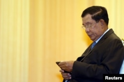 FILE - Cambodia's Prime Minister Hun Sen looks at his smartphone at a ceremony in Phnom Penh, Feb. 25, 2016.