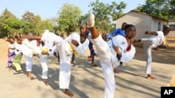 Natsiraishe Maritsa, second right, goes through taekwondo kicking drills during a practice session with young boys and girls in the Epworth settlement about 15 km southeast of the capital Harare, Saturday Nov. 7, 2020.