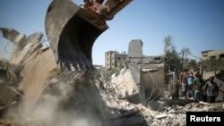 ຊາວປາແລສໄຕນ໌ ພາກັນໄປຫຸ້ມເບິ່ງ ພວກຊອກຄົ້ນຫາສົບ ຢູ່ກ້ອງສິ່ງຫັກພັງ ໃນເຮືອນຫຼັງນຶ່ງທີ່ຖືກໂຈມຕີທາງອາກາດ ຂອງອິສຣາແອລ ໃນເຂດ Beit Lahiya ພາກເໜືອຂອງ ເຂດກາຊາ, ວັນທີ 25 ສິງຫາ 2014.