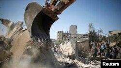 Beyt Lahiye kasabasında hava saldırısında yıkılan bir evin enkazını kaldırmaya çalışan Filistinliler