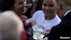 올해 초 미국 사우스캐롤라이나주 워터루 유세에서 지지자가 내민 현금에 사인해주고 있는 도널드 트럼프(오른쪽) 공화당 대통령 후보. (자료사진)