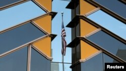 FILE - The U.S. flag is reflected on the windows of the U.S. Embassy in Kabul, Afghanistan, July 30, 2021.