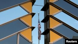 The U.S. flag is reflected on the windows of the U.S. Embassy in Kabul, Afghanistan, July 30, 2021.