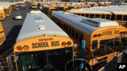 FILE - Los Angeles School District buses are parked at their bus garage in Gardena, California, Dec. 15, 2015.